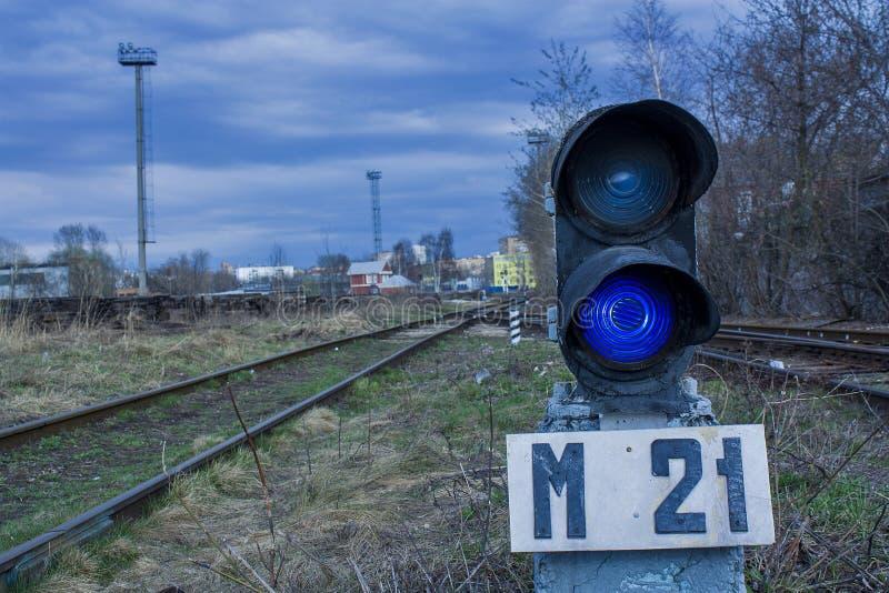 Il semaforo accende il blu accanto alla ferrovia immagine stock