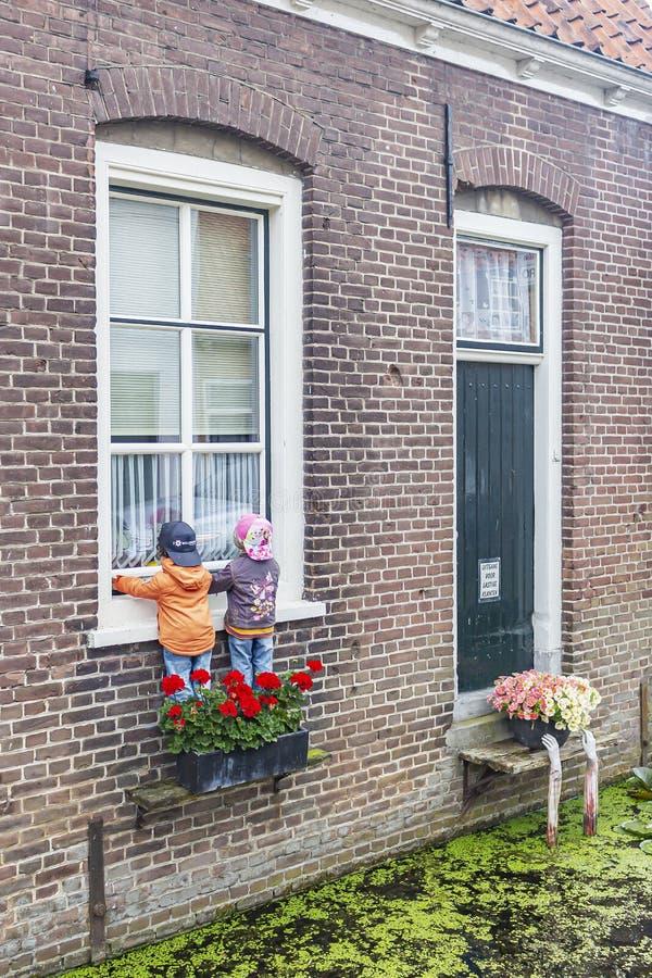 Il semble comme ces deux enfants que les marionnettes aiment monter par la note de fenêtre également la sortie spéciale pour les  images stock