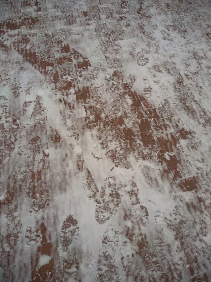 Il sentiero per pedoni è spruzzato con neve bianca con le tracce di calzature umane immagini stock libere da diritti