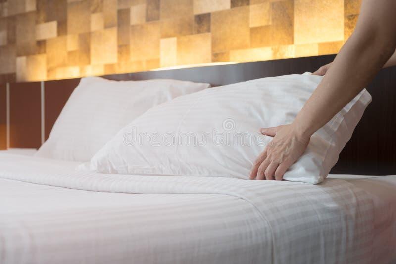 Il servizio di camera di albergo passa a messa a punto il cuscino bianco sul letto nella h immagine stock