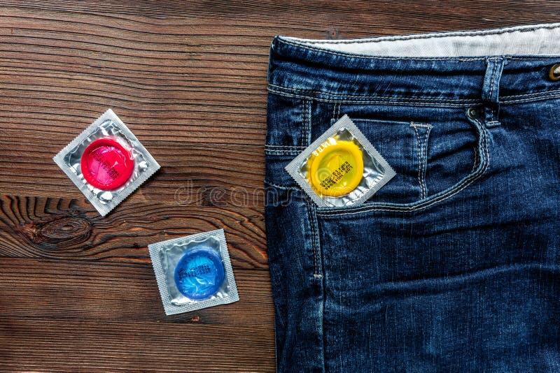 Il sesso sicuro con la contraccezione del preservativo in jeans intasca sulla vista superiore del fondo di legno fotografia stock