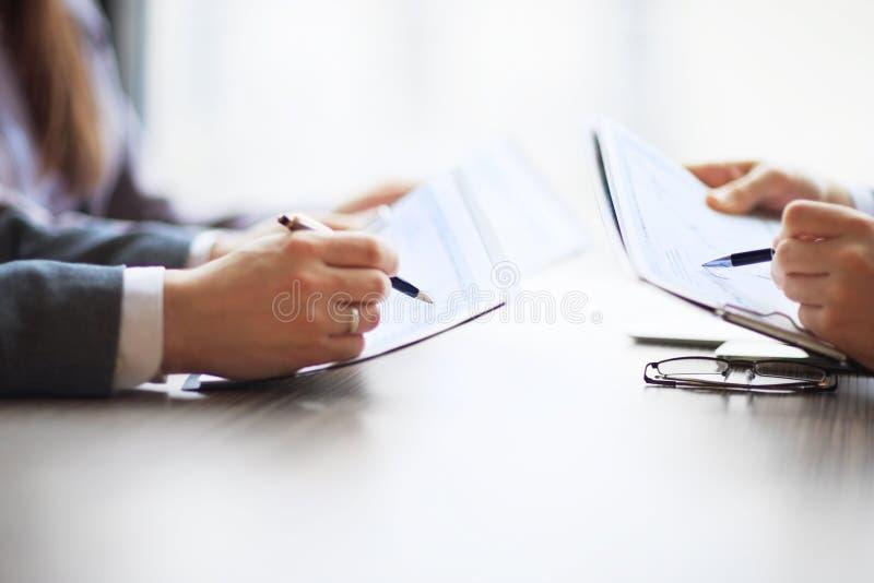Il settore bancario nei grafici di contabilità da tavolino dell'analista finanziario, penne indica i grafici immagine stock