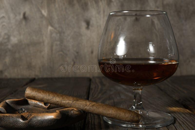 Il sigaro nel portacenere ed in un vetro del cognac sulla quercia ha strutturato la tavola immagini stock libere da diritti
