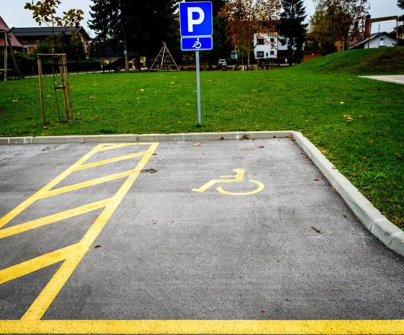 Il simbolo della sedia a rotelle nelle indicazioni della partita di parcheggio ha disattivato il posto-macchina immagine stock libera da diritti