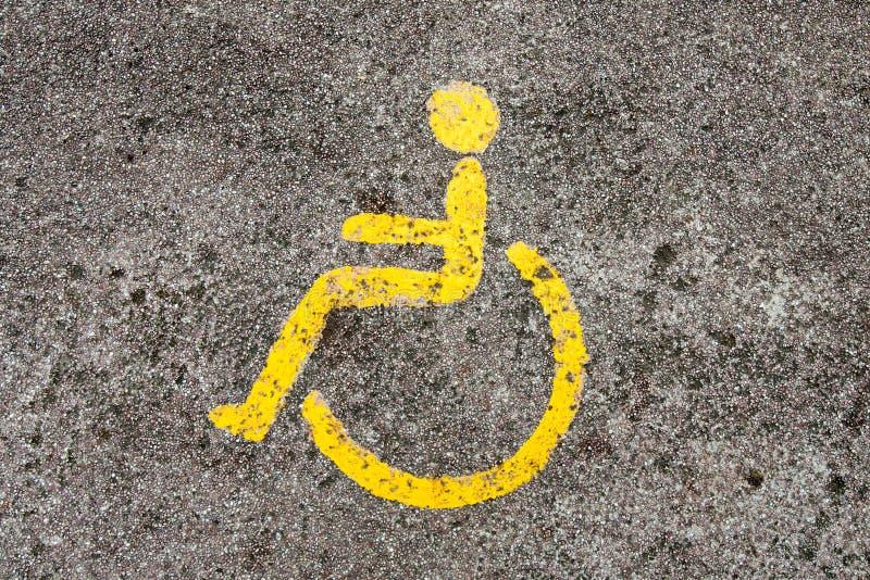 Il simbolo della sedia a rotelle sul modo della passeggiata nel giardino del ther immagine stock
