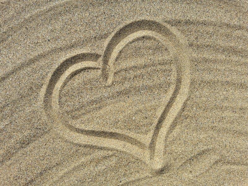 Il simbolo di amore attinge la sabbia immagini stock libere da diritti