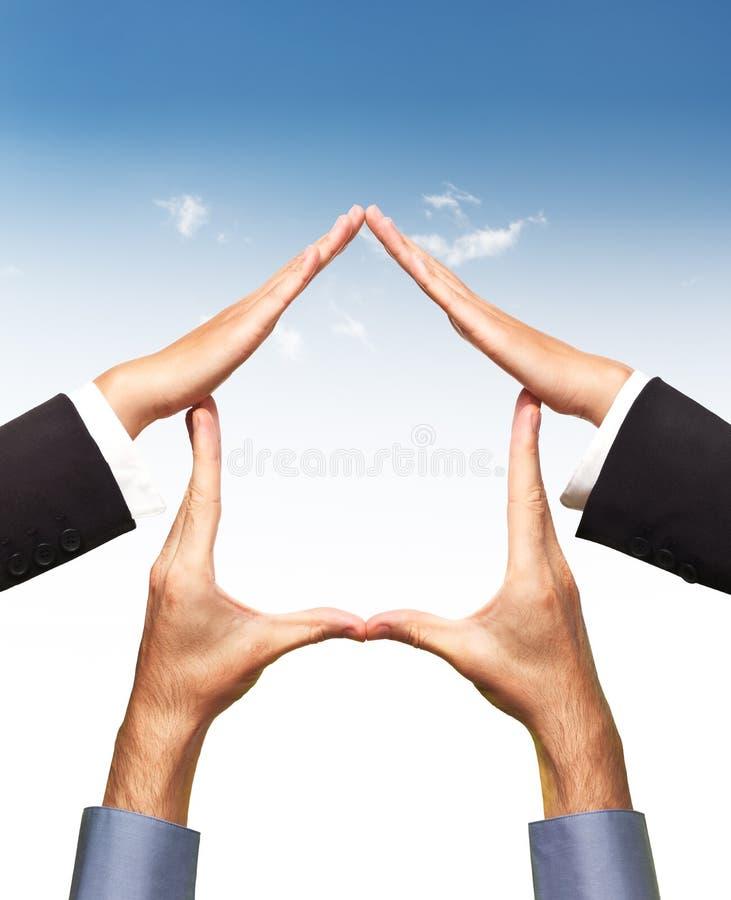 Il simbolo domestico concettuale fatto vicino consegna il cielo blu fotografia stock