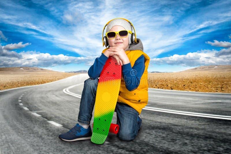 Il skateboarder del ragazzo sta riposando sulla strada fotografia stock