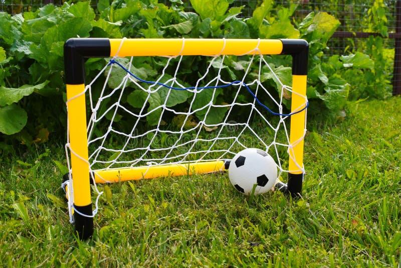Il soccerball dei bambini in portone Gioco di sport nell'aria fresca immagine stock