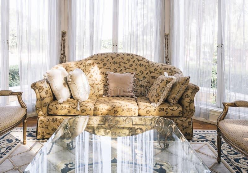 Il sofà con la tavola dei cuscini ha messo con stile floreale del classico del tessuto fotografia stock