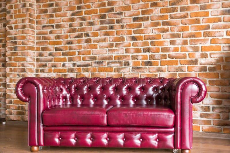 Il sofà di cuoio rosso sta sui precedenti del muro di mattoni immagine stock