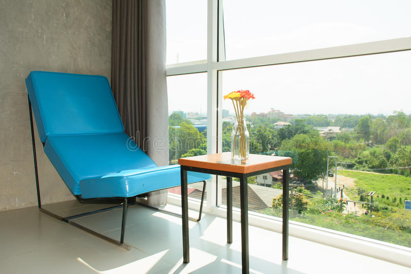 Il sofà ed il fiore blu dentro si rilassano il tempo fotografia stock libera da diritti