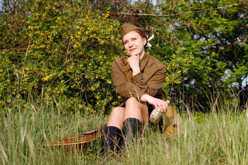 Il soldato femminile sovietico in uniforme della seconda guerra mondiale si siede con la boccetta su erba fotografia stock
