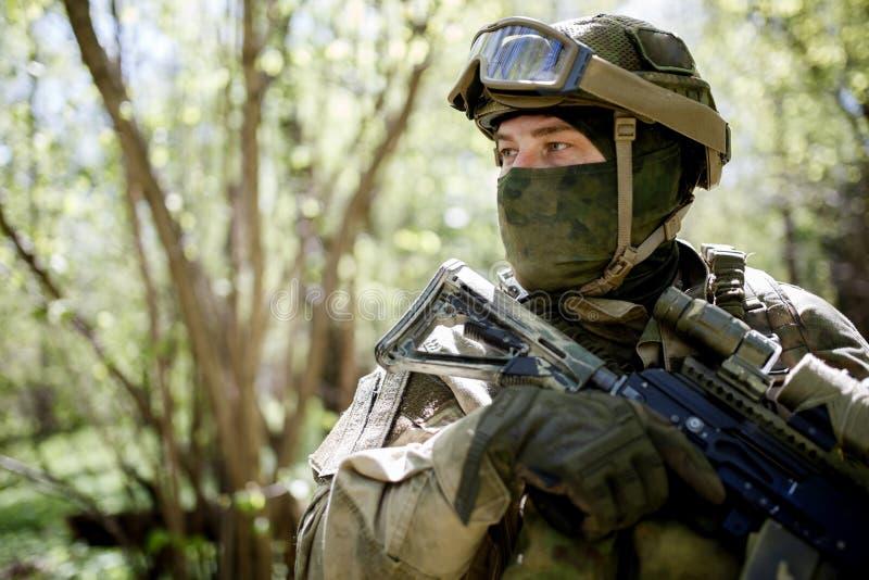 Il soldato negli occhiali di protezione guarda lateralmente fotografia stock