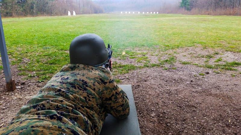 Il soldato nel dipartimento militare, con un casco sul suo capo, si trova sulla terra e mira all'obiettivo fotografie stock libere da diritti