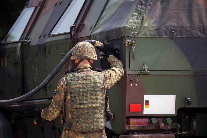 Il soldato rifornisce un camion di combustibile corazzato militare fotografie stock