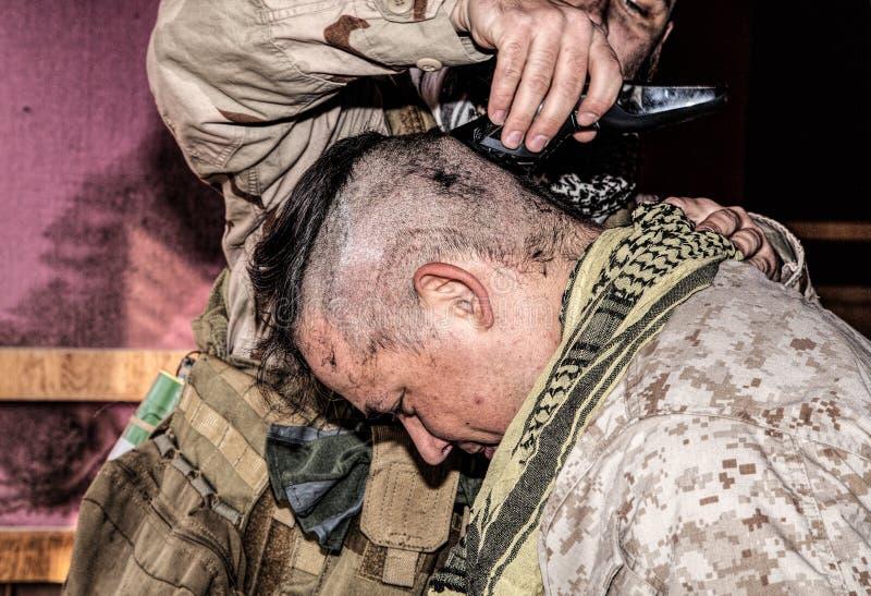Il soldato taglia i capelli di camerati con il regolatore o il tagliatore immagini stock