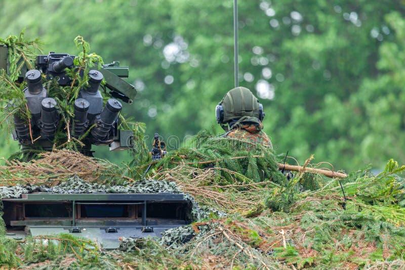 Il soldato tedesco si siede su un militare completamente ha cammuffato il veicolo fotografia stock