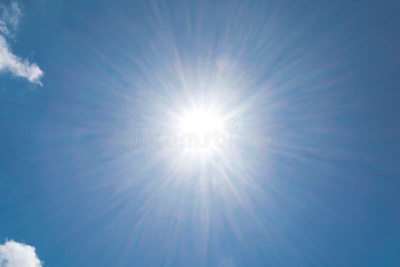 Il sole brillante realistico con il chiarore della lente su cielo blu si appanna il fondo del giorno della natura fotografia stock libera da diritti