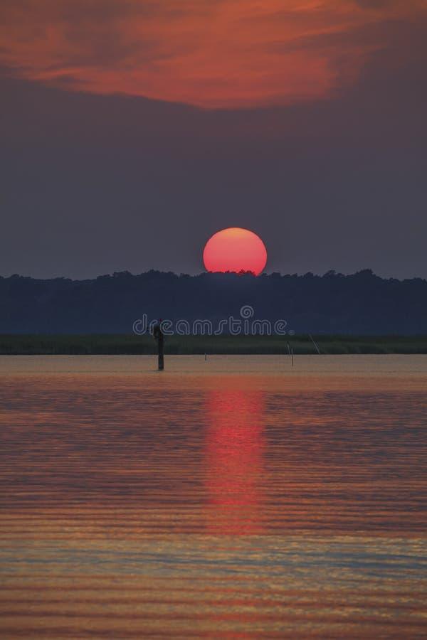 Il sole cala sul fiume fotografie stock