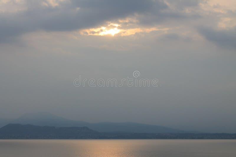 Il sole che attraversa si rannuvola la polizia Italia del lago fotografie stock