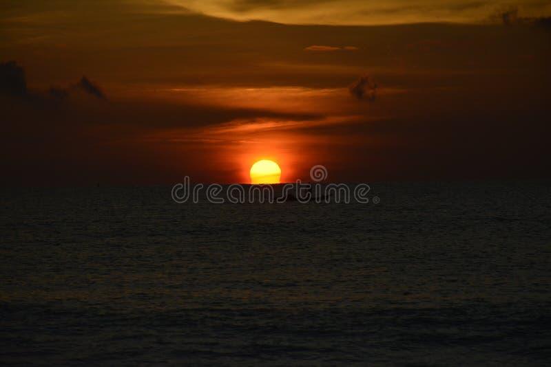 Il sole che sbircia fuori da sotto immagine stock