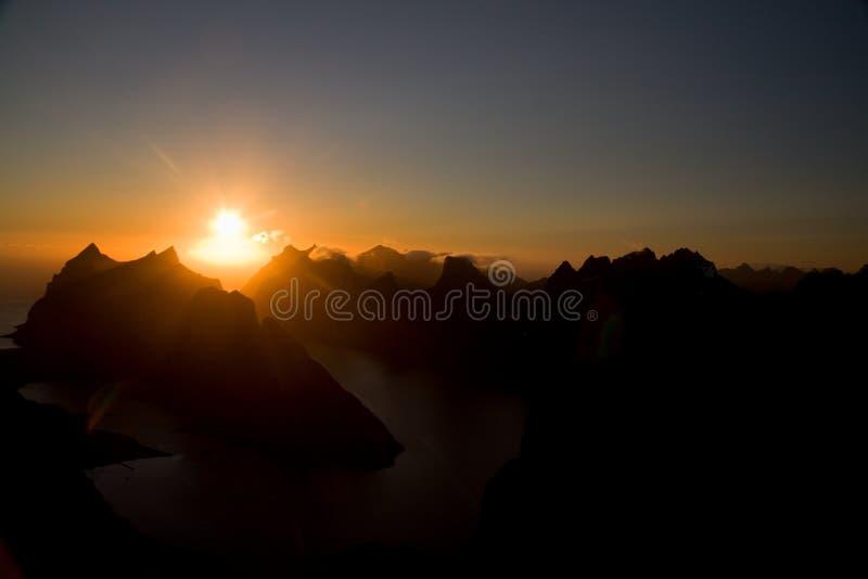 Il sole di mezzanotte di Lofoten sopra le montagne taglienti di Moskenesoya vedute dalla sommità, dal tramonto e dall'alba del pi immagini stock libere da diritti