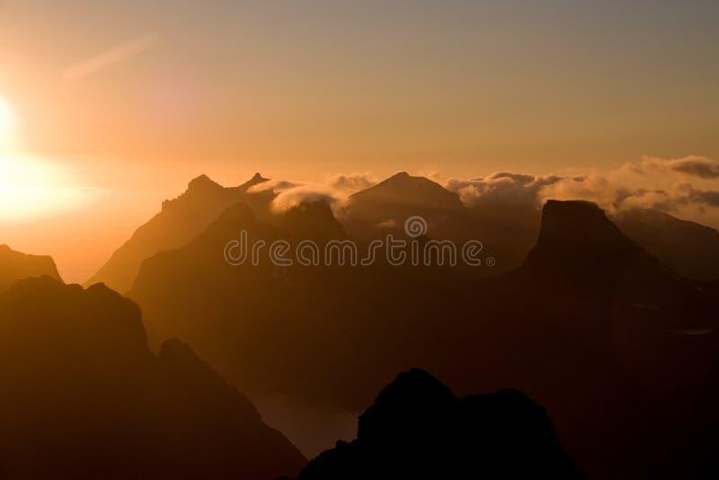 Il sole di mezzanotte di Lofoten sopra le montagne taglienti di Moskenesoya vedute dalla sommità, dal tramonto e dall'alba del pi fotografie stock