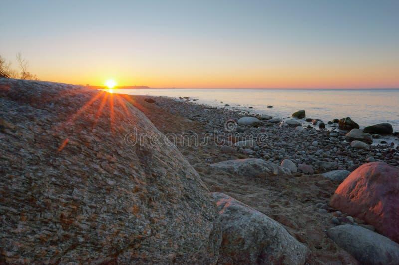 Il sole e un grande masso del mare, il sole mette sopra l'orizzonte di mare immagine stock