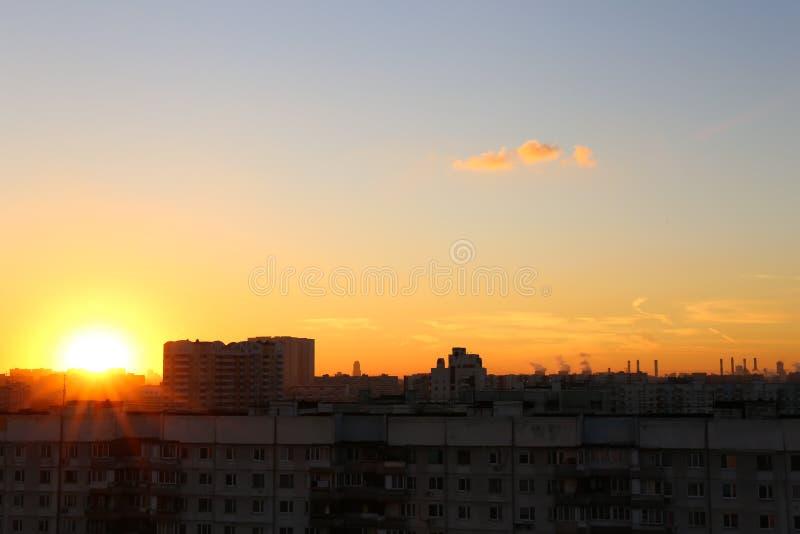 Il sole mette dietro le case fotografie stock