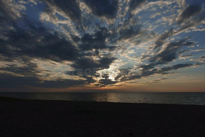 Il sole mette sopra un grande lago immagine stock