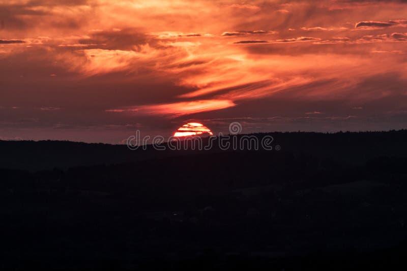 Il sole scompare dietro le montagne immagine stock