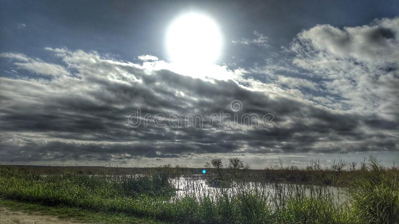 Il sole splende tra le nuvole sulla palude fotografie stock