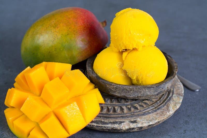 Il sorbetto del gelato del mango con le foglie di menta ed il mango fruttificano nel nero fotografia stock