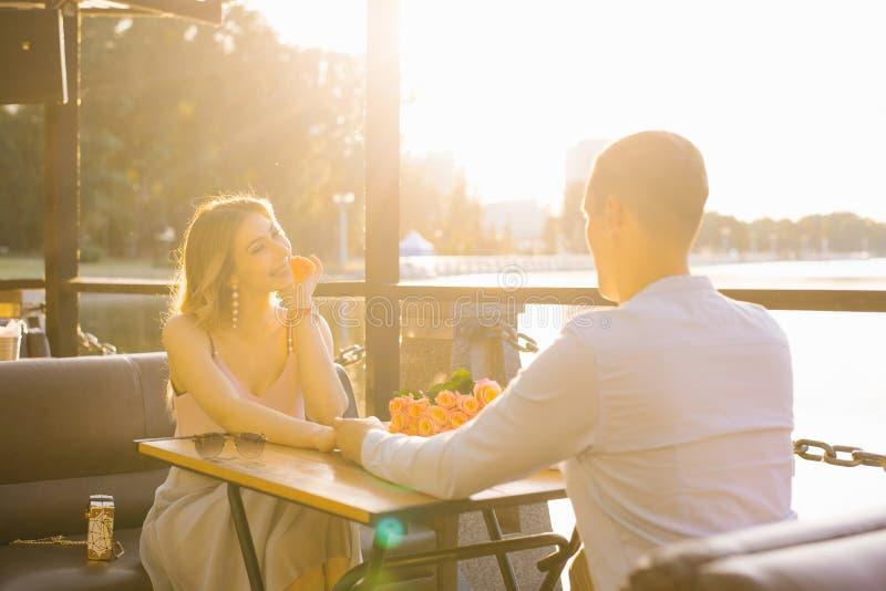 Il sorriso felice della ragazza e del tipo e se tiene per mano, esamina la tavola del caffè dell'estate il tramonto fotografia stock libera da diritti