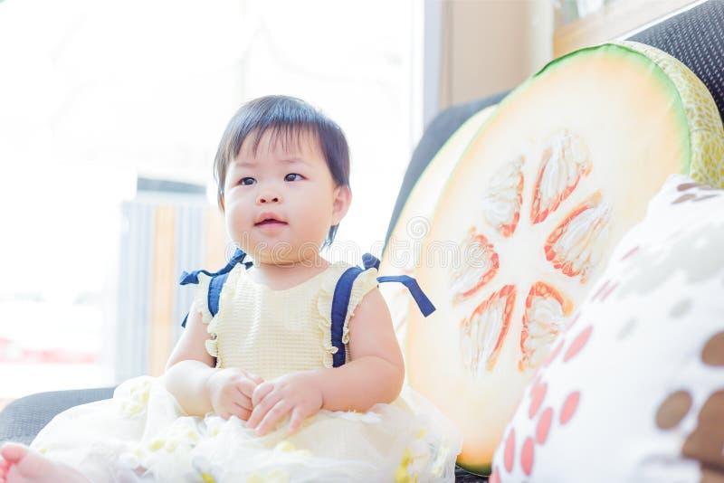 Il sorriso sveglio della neonata e sedersi sul sof? fotografia stock
