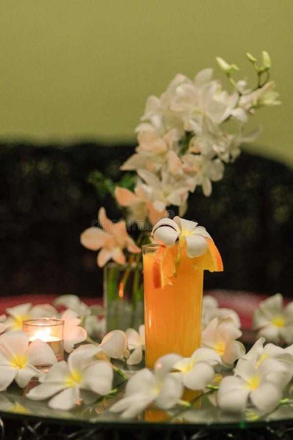 Il succo d'arancia fresco di recente schiacciato con la magnolia sboccia su Th immagini stock libere da diritti
