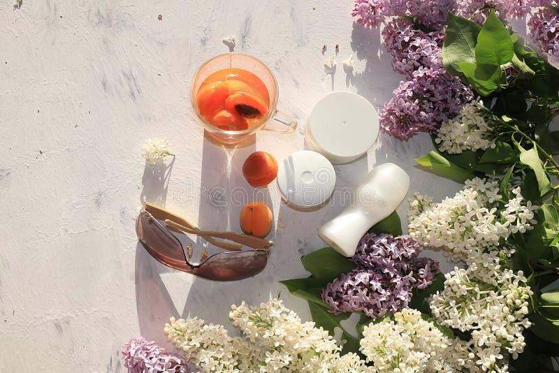 Il succo di albicocca, albicocche, su una tavola soleggiata accanto a screma per cura ed il deodorante del corpo, preparando per  fotografia stock