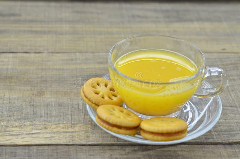 Il succo di ananas schiacciato con i biscotti si inceppa sulla tavola di legno fotografia stock libera da diritti