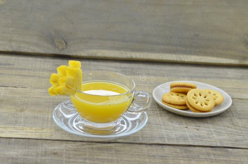 Il succo di ananas schiacciato con i biscotti si inceppa sulla tavola di legno immagini stock