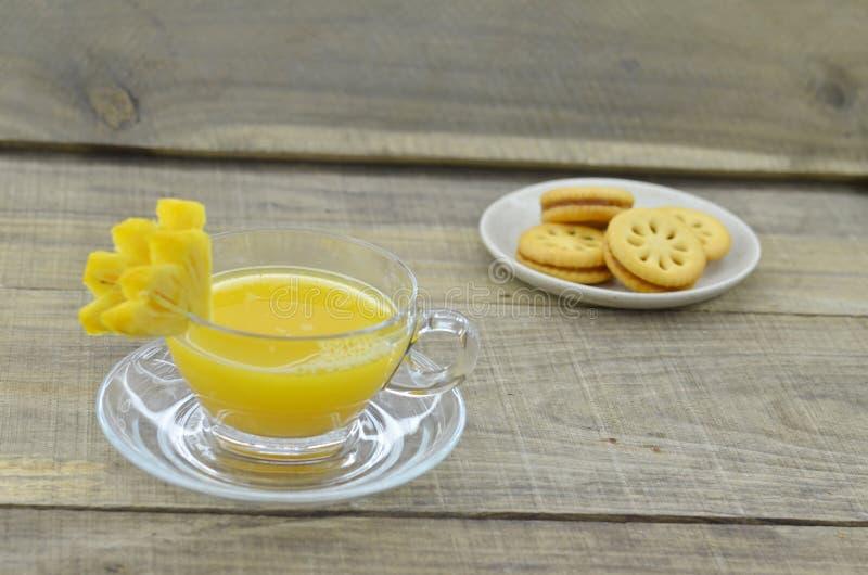 Il succo di ananas schiacciato con i biscotti si inceppa sulla tavola di legno fotografie stock