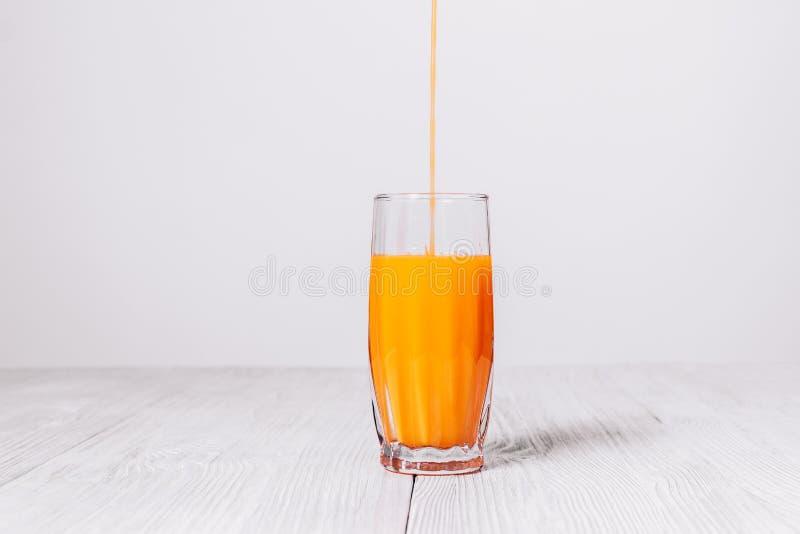 Il succo di arancia è versato in un vetro fotografia stock