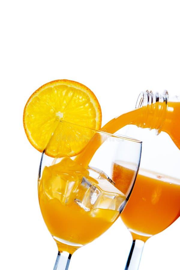 Il succo di arancia ha versato dentro un vetro fotografie stock