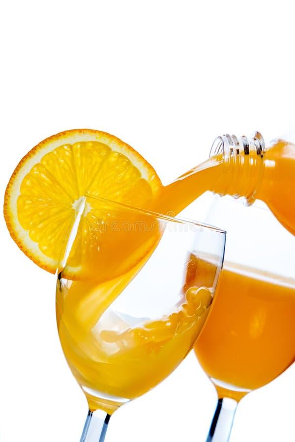 Il succo di arancia ha versato dentro un vetro fotografia stock libera da diritti
