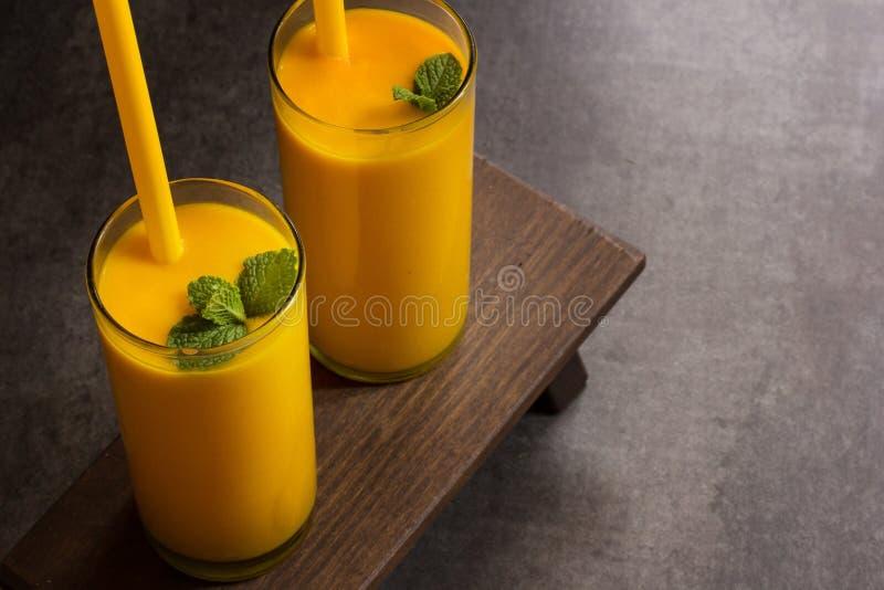 Il succo di Lassi Smooothie del mango con paglia al di sopra osserva fotografia stock libera da diritti
