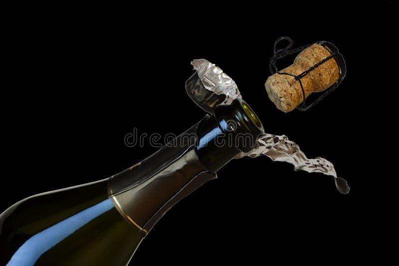 Il sughero decolla da una bottiglia di champagne isolata su un fondo nero fotografia stock