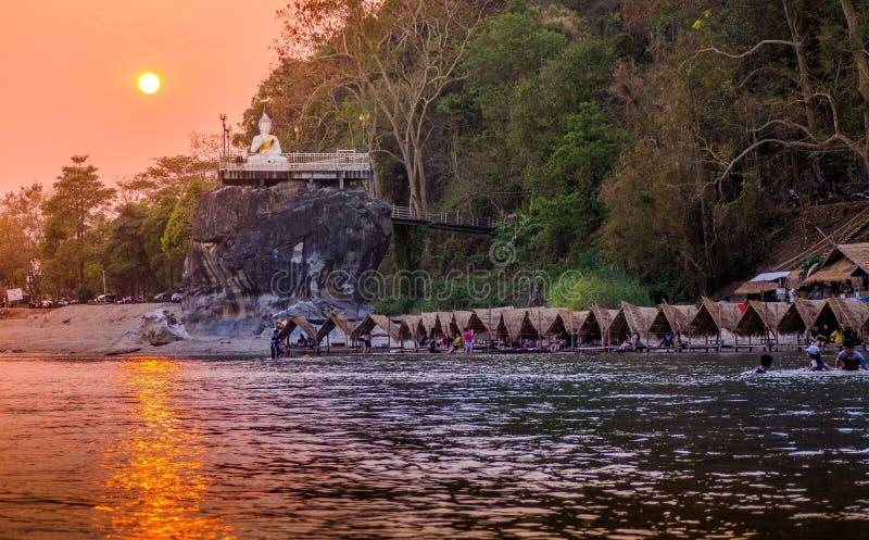 Il Sun cade vicino al fiume con la statua di Buddha immagine stock libera da diritti