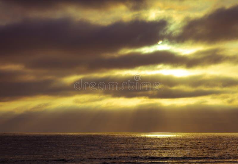 Il Sun si irradia attraverso una nuvola e crea il riflettore dell'oceano immagine stock libera da diritti
