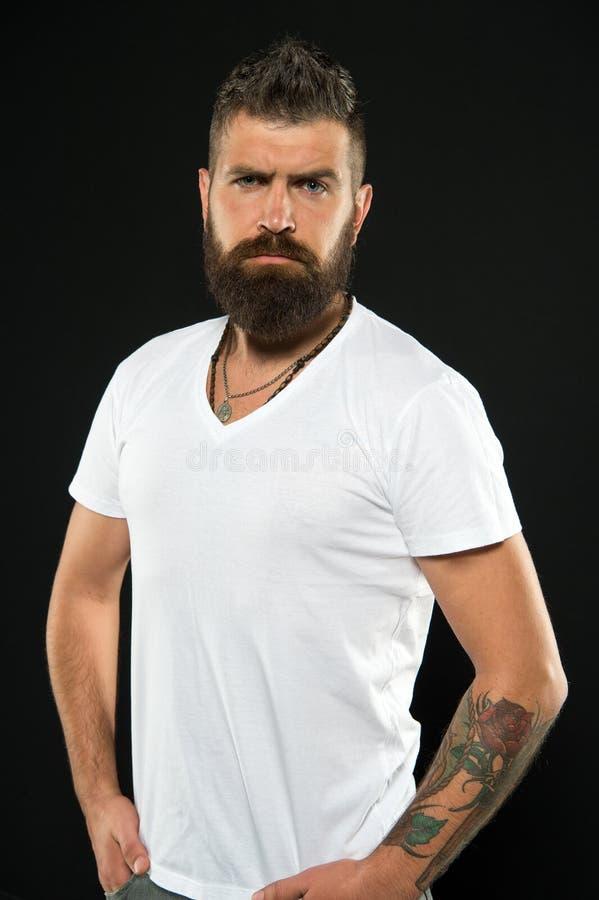 Il suo barbiere ha un esperto Barbiere serio su fondo nero Uomo barbuto con i capelli a forma di dei baffi e della barba dopo fotografia stock