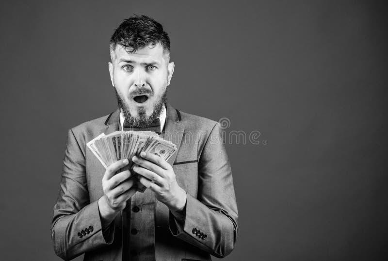 Il suo primo stipendio Mediatore di valuta con il pacco di soldi Uomo barbuto che tiene denaro contante Uomo d'affari ricco con i fotografia stock